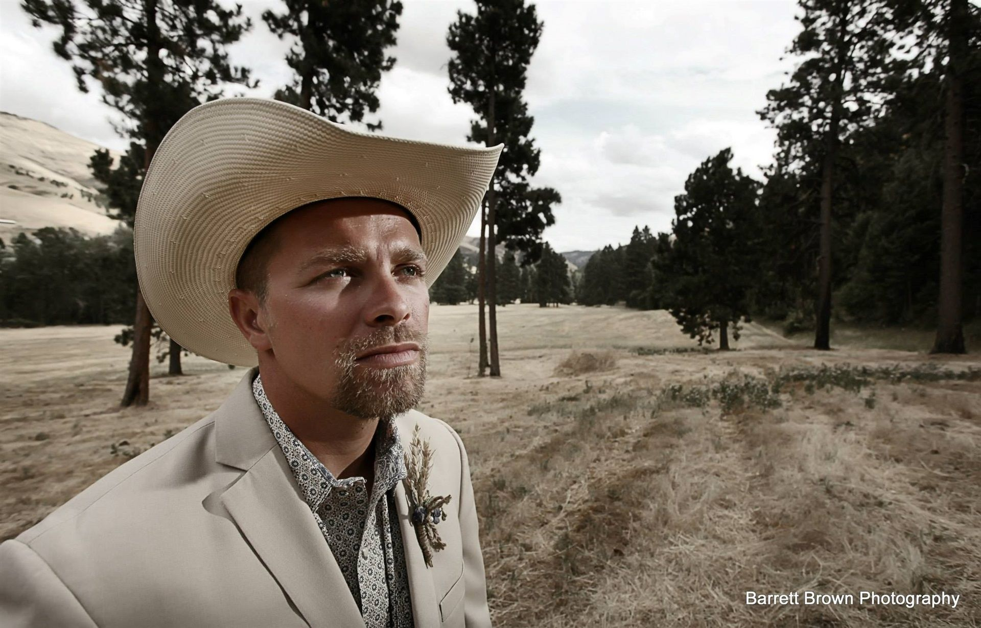 Groom in a field wearing 10-gallon hat and suit