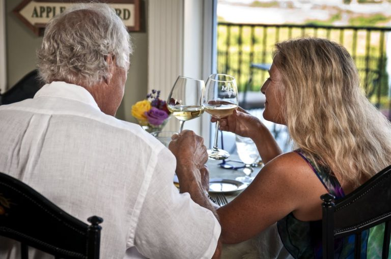 Older Couple toast their getaway with white wine