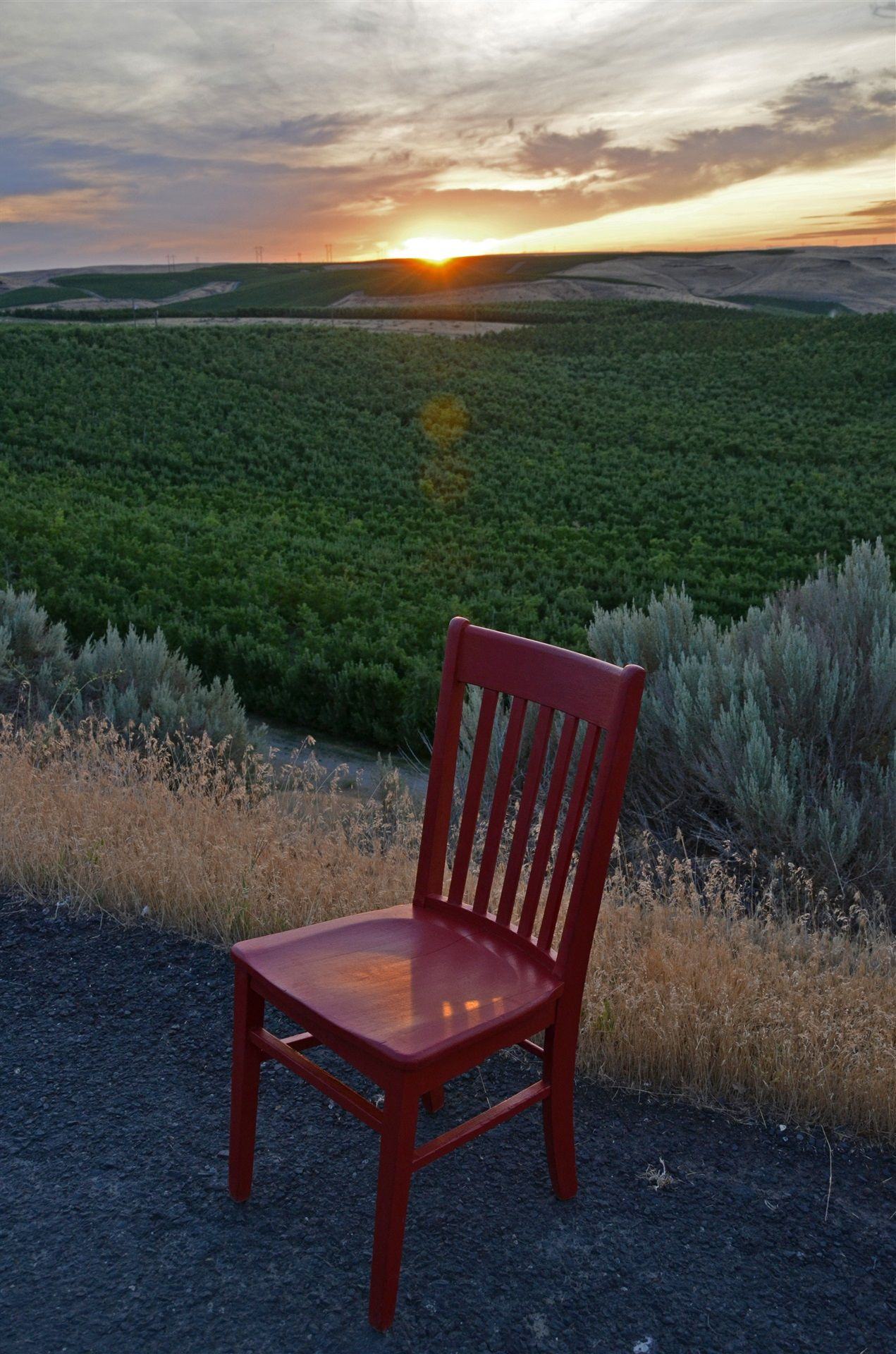 Red chair on gravel road overlooking the forests and mountain during the sunrise