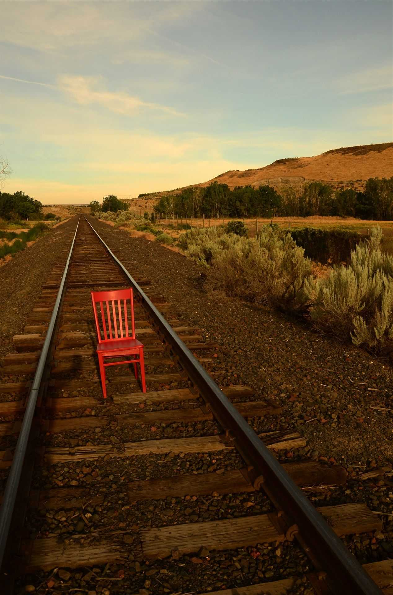 Red chair put on a railroad tie in the middle of the tracks as they go off into the distance