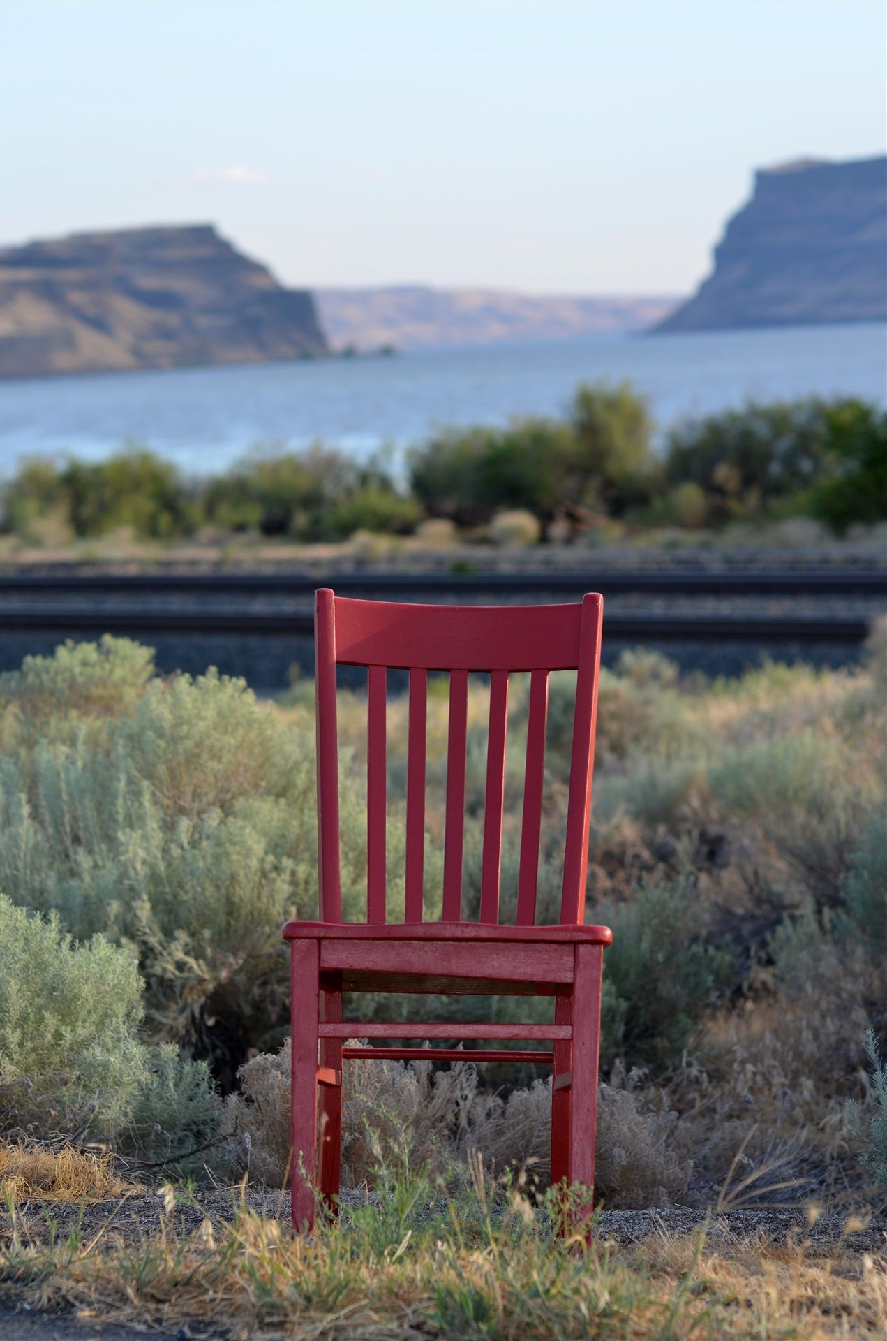 Red chair sitting amongst some brush with the bay and cliffsides in the background