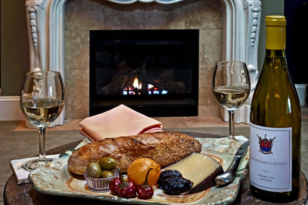Greek Suite fireplace with plated dinner and two glasses of Chardonnay with the bottle beside the plate