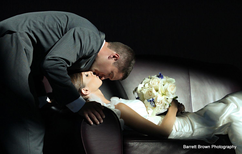 Groom kissing bride as she lies on a couch like Sleeping Beauty