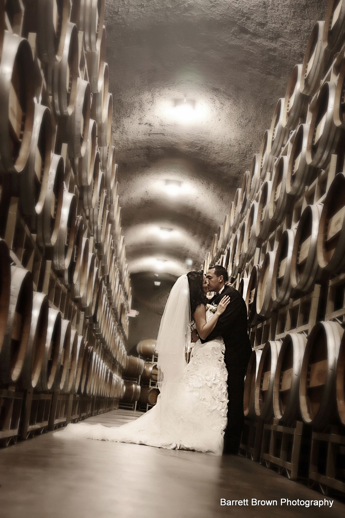 Groom dipping bride while the couple kiss in a warehouse between two four-barrel high alcohol fermentation barrels