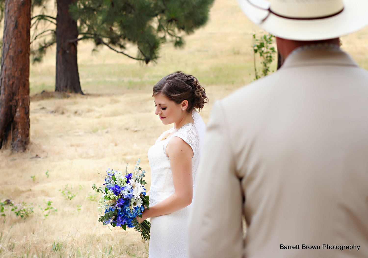 Bride in a field with two trees, holding bouquet of mostly blue flowers with man in hat and suit standing in foreground