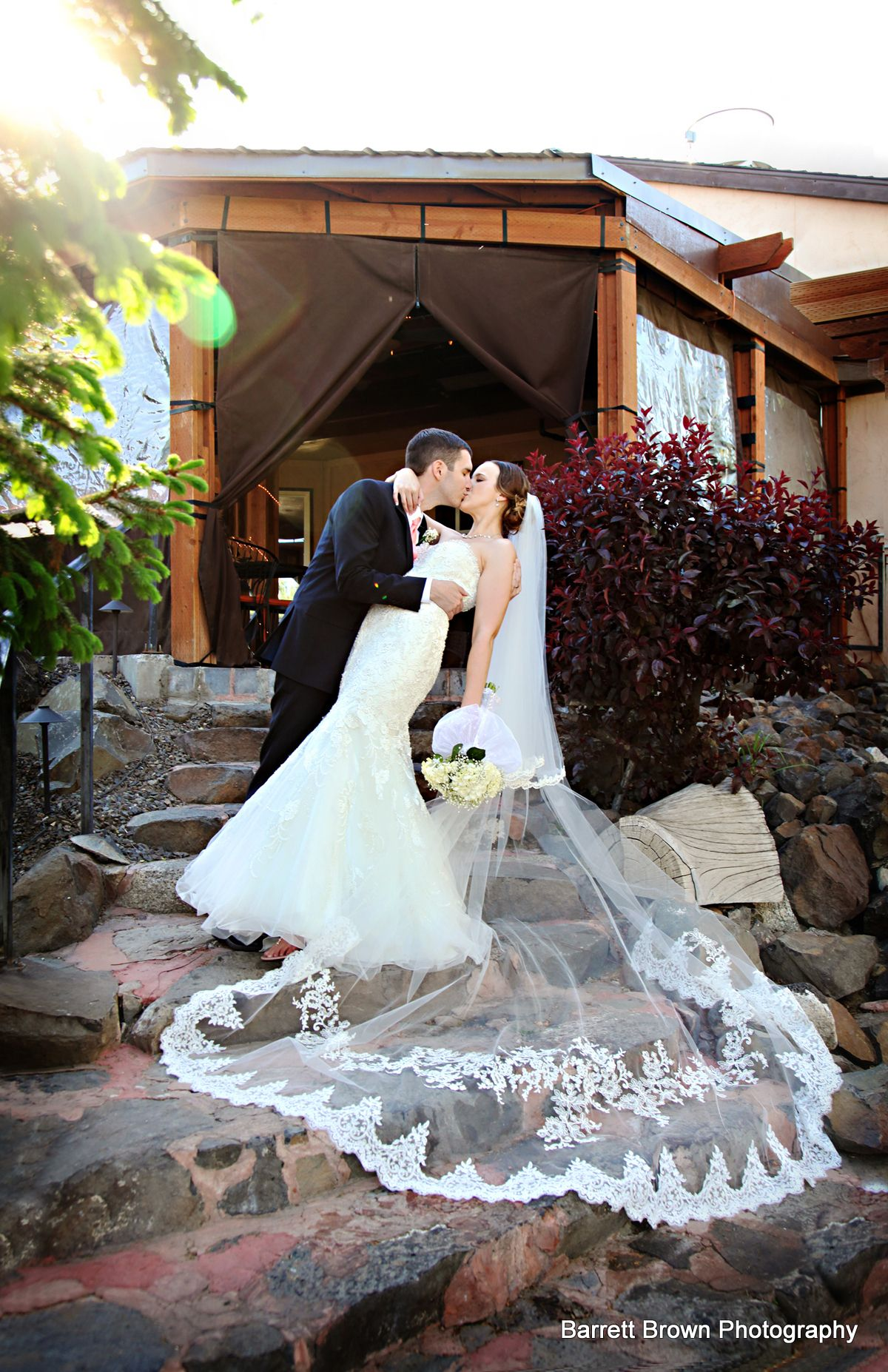 Groom dipping bride as the couple kiss on a stone staircase