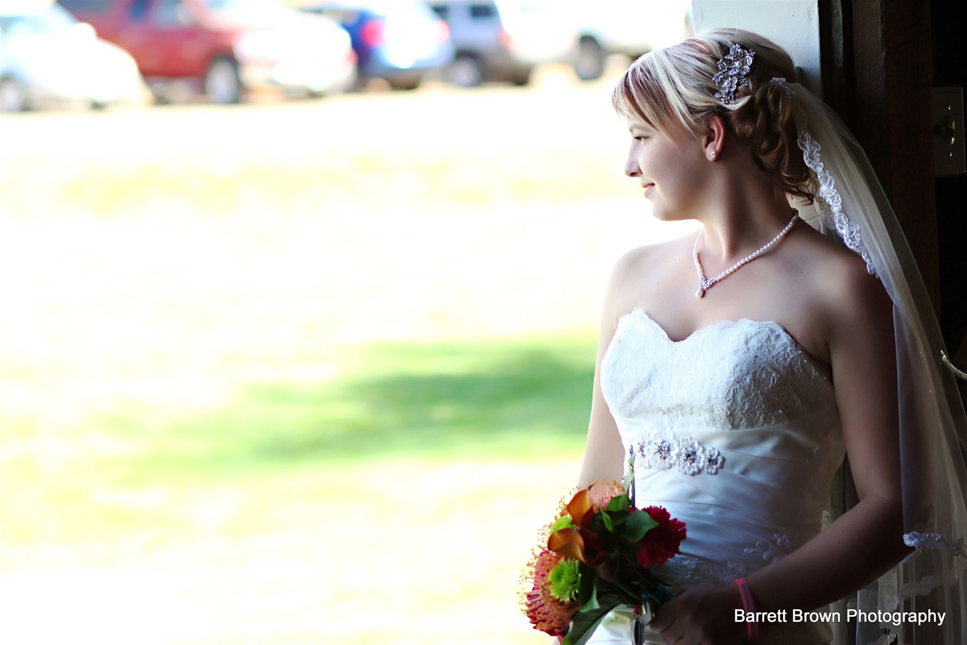 Bride, holding a red and white bouquet, looking out to blurred field