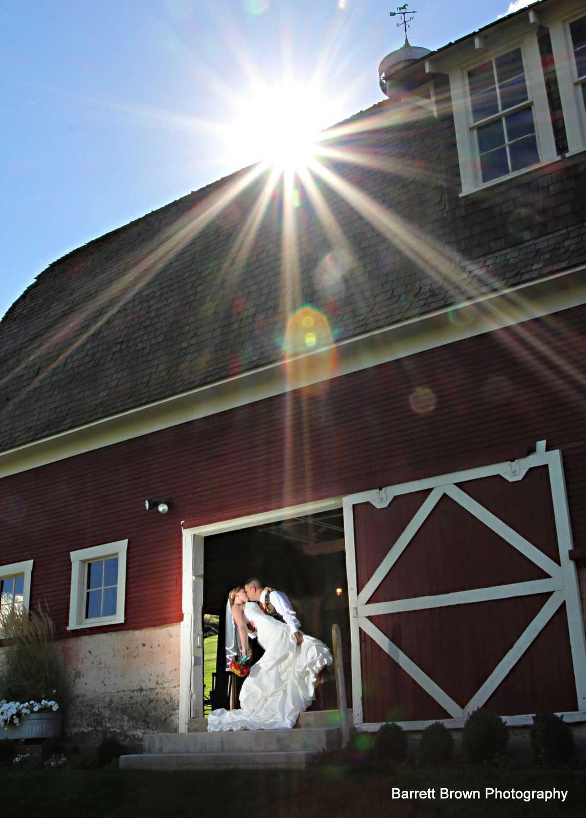 Groom dipping his bride as the couple kiss at the center of an open bar door, the sun peeking over