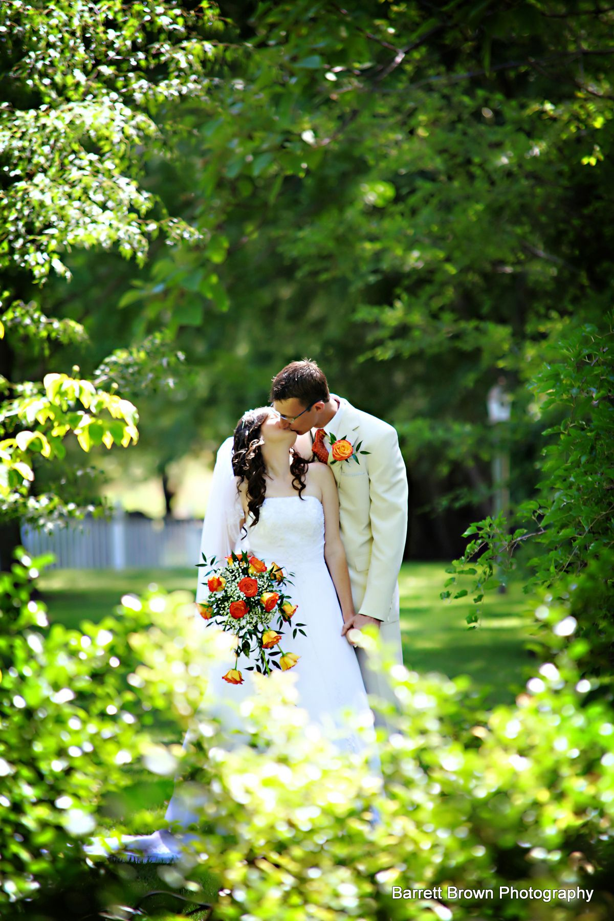 Bride and groom kissing in a lightly forested field
